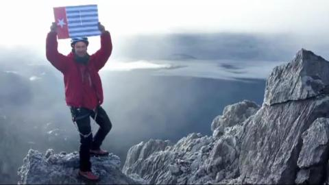 Christian  Welponer a world famous mountaineer flies the Morning Star flag on the peak of the highest mountain in West Papua in defiance of the Indonesian authorities.